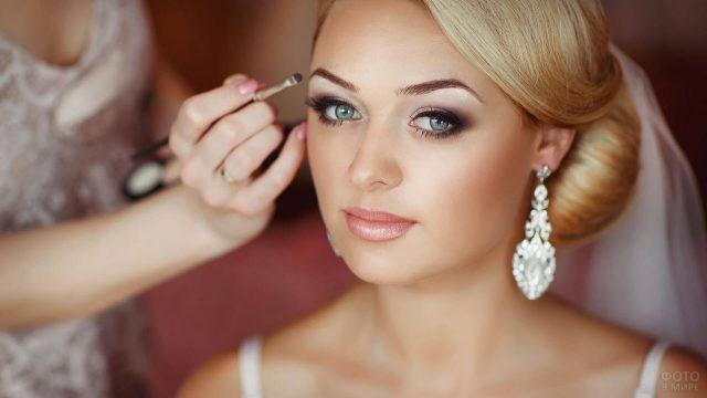 Невесте наносят макияж