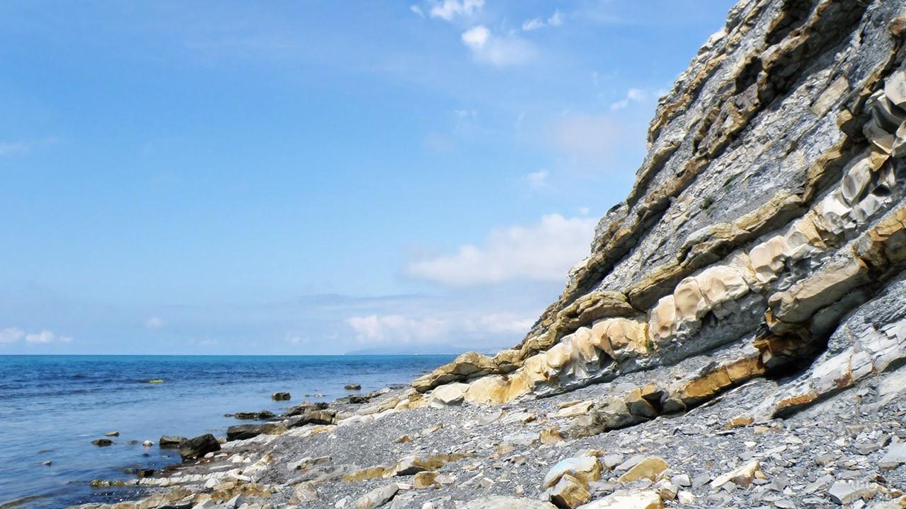 Красивый дикий пляж под скалой