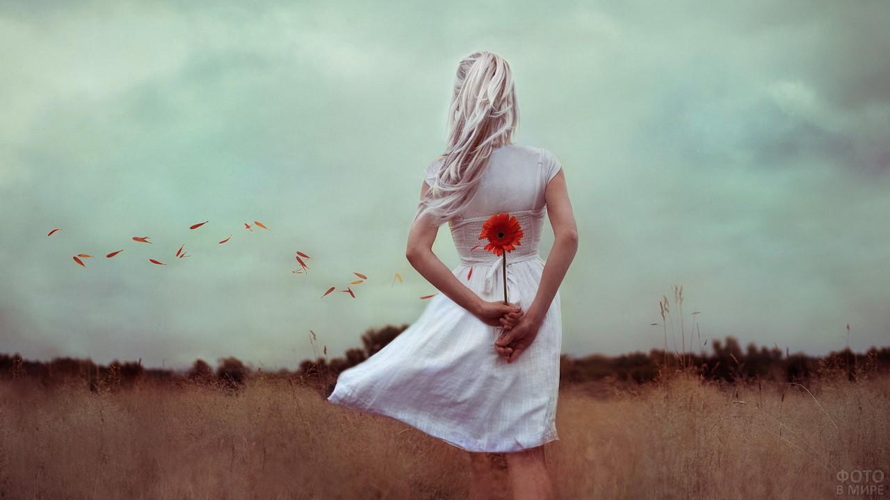 Блондинка с красной герберой за спиной