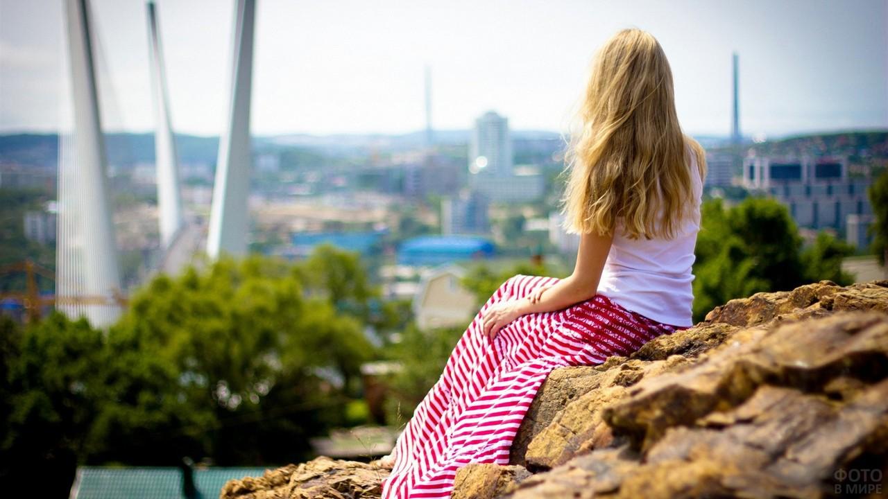 Блондинка в красно-белой юбке на камнях