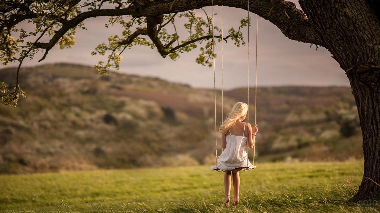 Девушка на привязанных к дереву качелях