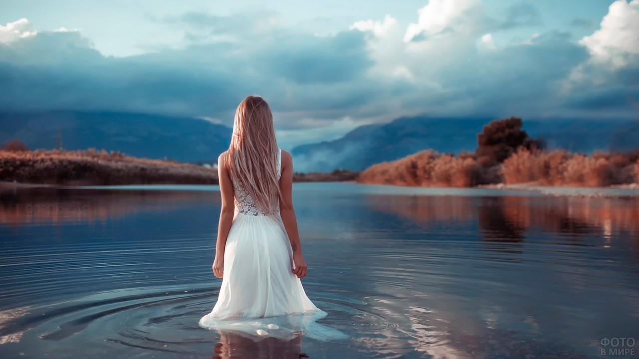 Девушка в белом платье идёт в озеро