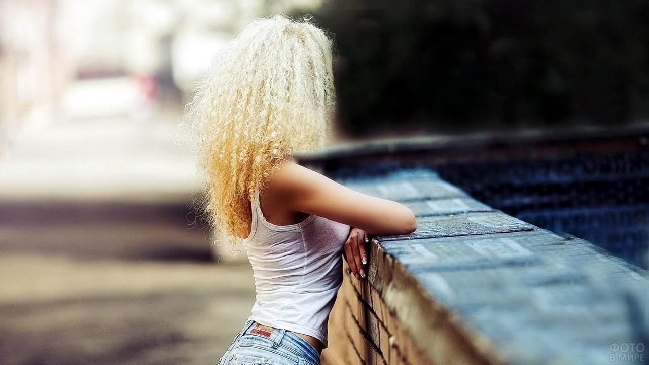 Кудрявая блондинка облокотилась на кирпичную стену