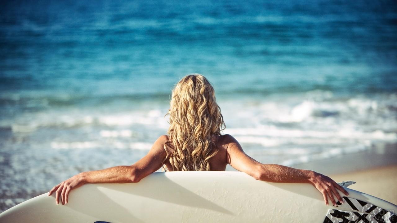 Сёрфингистка держит сёрф на пляже