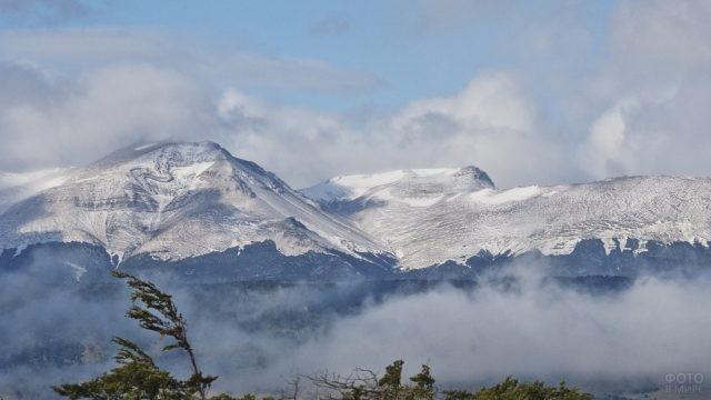 Густые облака проплывают над вершинами горной цепи