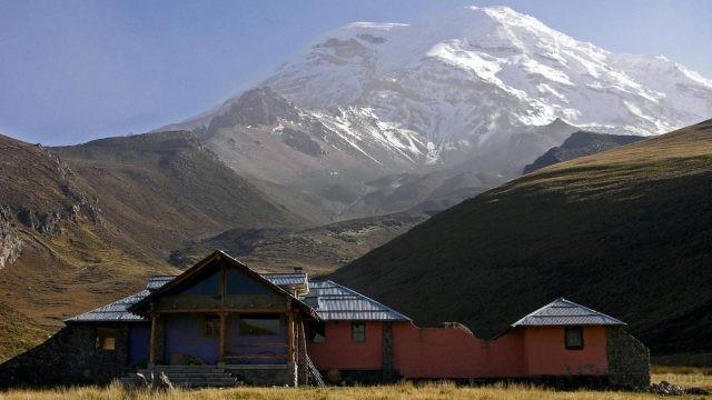 Небольшой домик, стоящий у подножия высоких гор