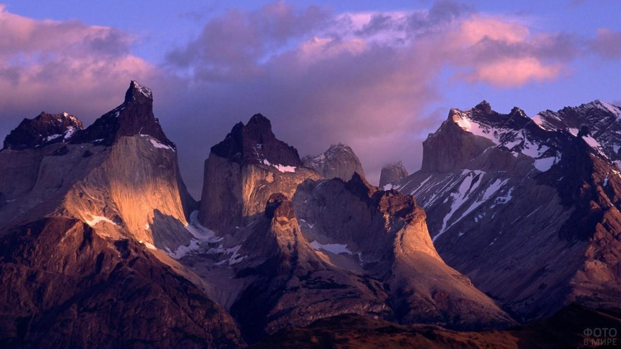 Солнечные лучи красиво падают на высокие горы сквозь облака