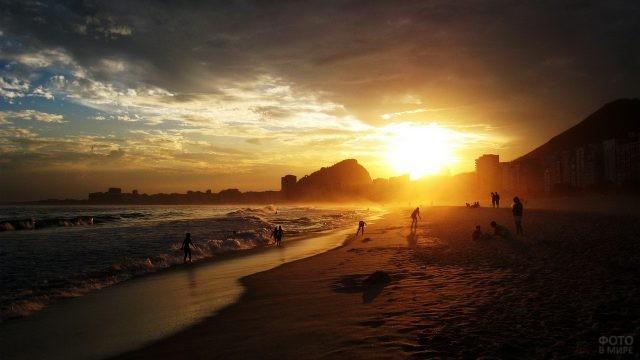 Люди купаются в волнах на закате