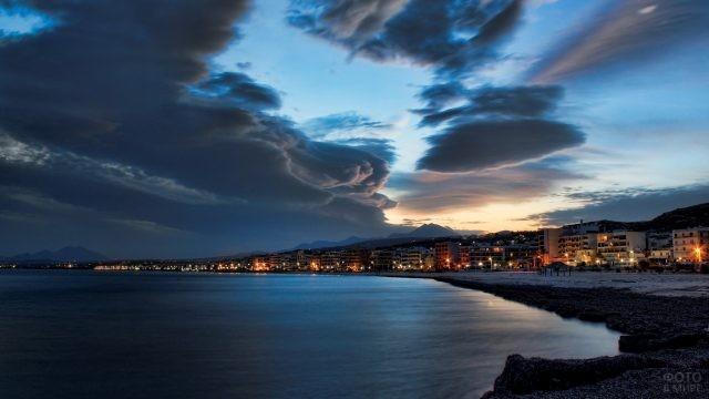 Облака над ночным городом у моря