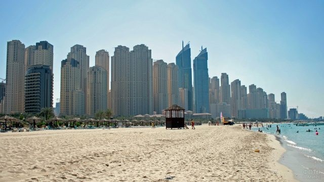 Широкий пляж с отдыхающими в Дубае