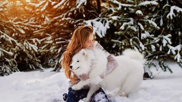 Девушка играет с белой собакой зимой