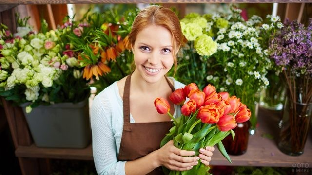Флорист в цветочном магазине с букетом
