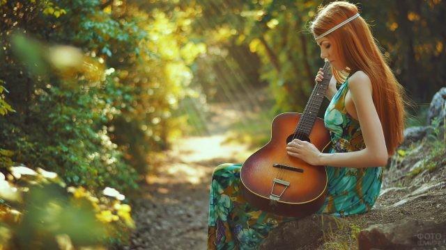 Гитаристка на камне в лесу