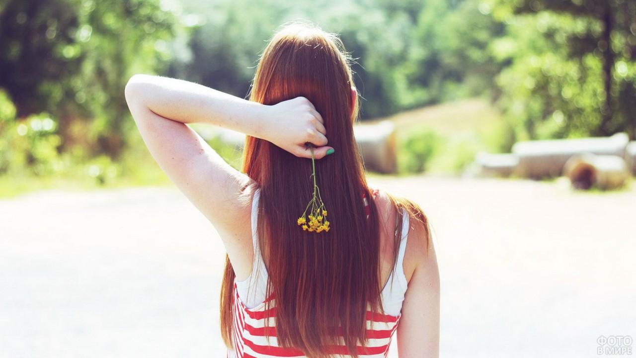 Рыжая девушка держит цветок за спиной