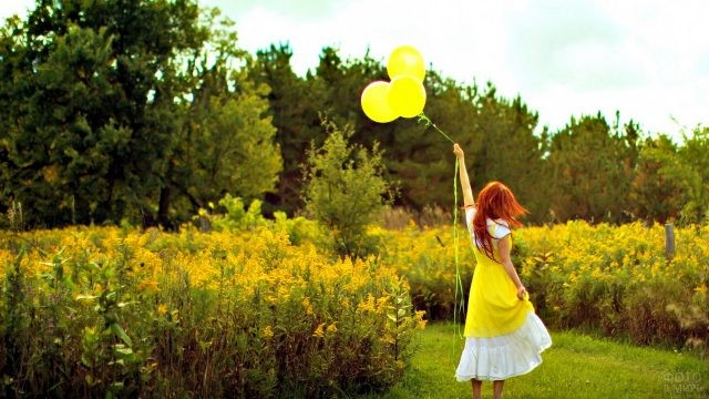 Рыжая девушка с жёлтыми шарами среди травы и деревьев
