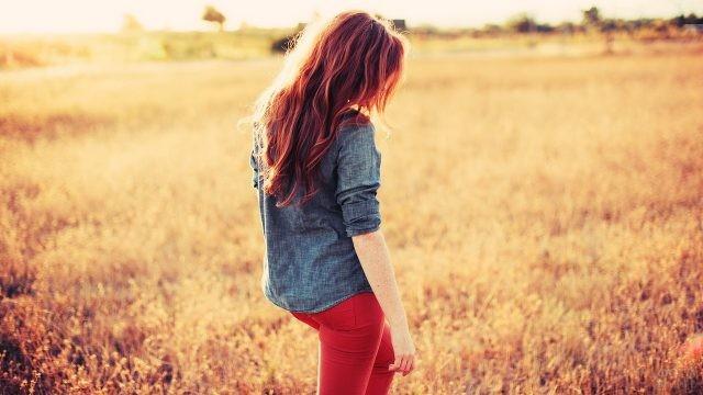 Рыжая девушка в красных брюках на поле