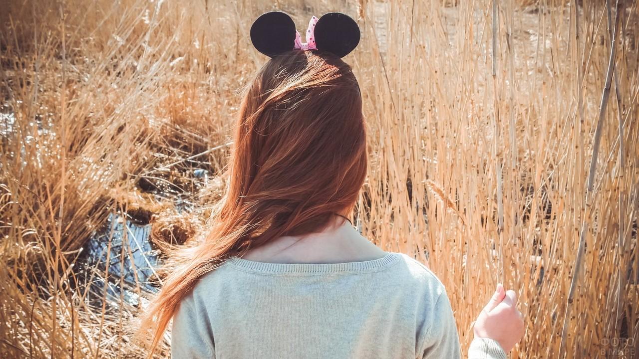 Рыжая девушка в ободке Мики-Маус в сухой траве