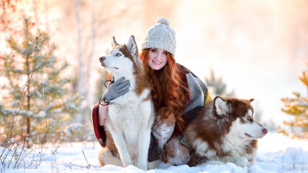 Рыжая девушка в шапке обнимает собак в зимнем лесу