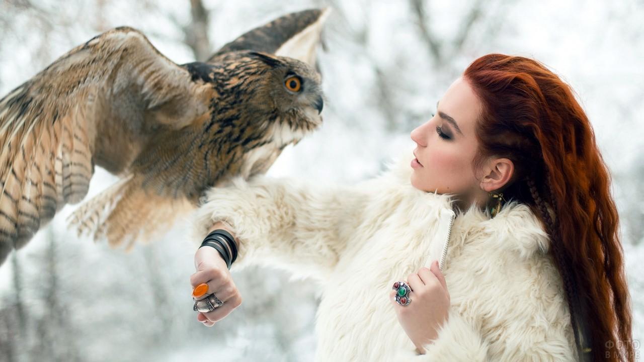 Смелая девушка в белой шубке с совой на руке