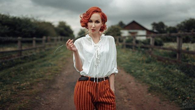 Уверенная девушка с соломинкой в зубах на ферме