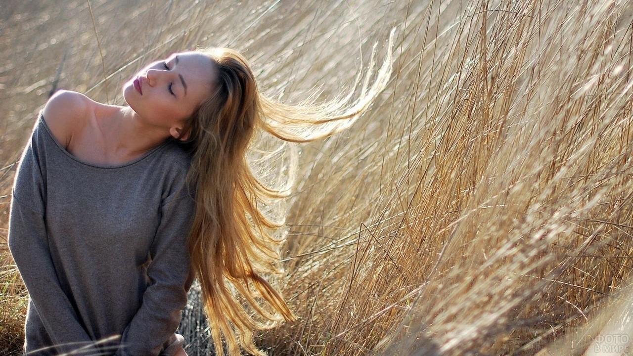 Девушка греется под лучами в сухой траве