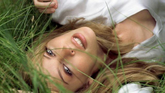 Девушка с русыми волосами лежит в траве