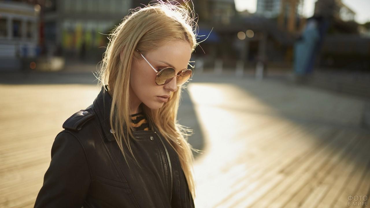 Девушка в солнцезащитных очках в кожаной куртке на улице