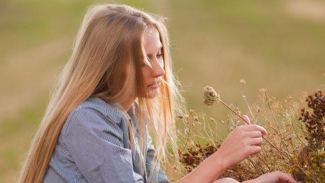 Русая девушка рассматривает траву в поле