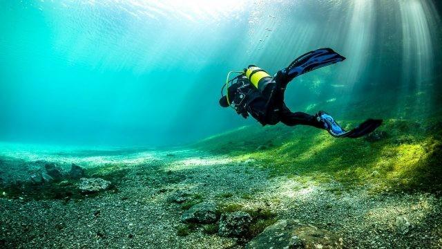 Дайвер в солнечных лучах под водой