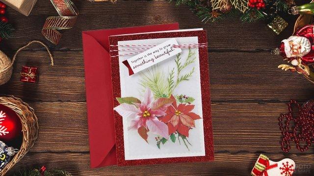 Красивая открытка с красным цветком среди рождественских украшений