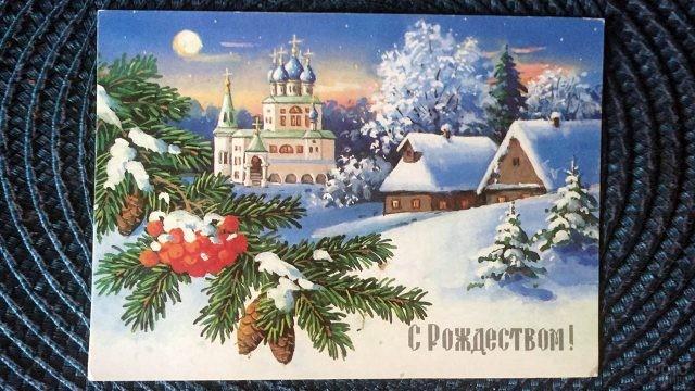 Почтовая рождественская открытка с еловой веткой на фоне церкви