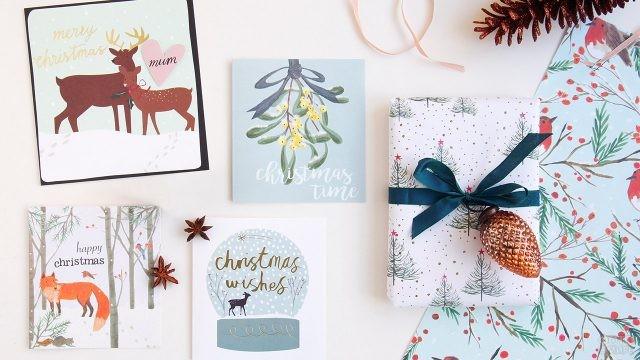 Рождественские открытки с нарисованными животными на столе с подарком