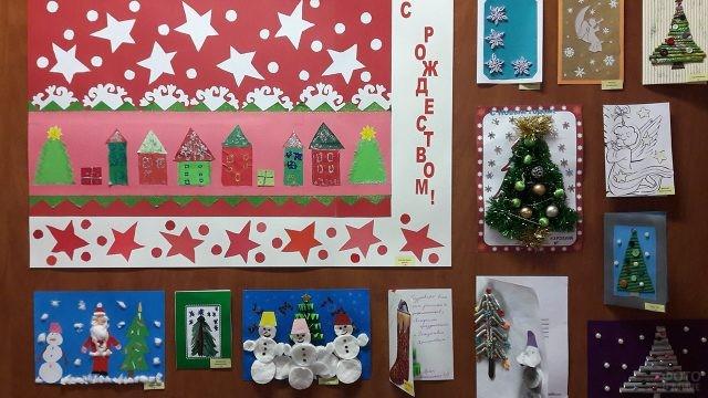 Самодельные рождественские открытки на стенде в детском саду