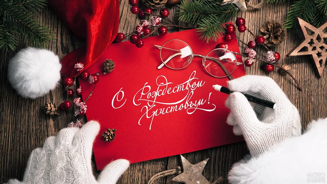 Санта подписывает рождественскую открытку