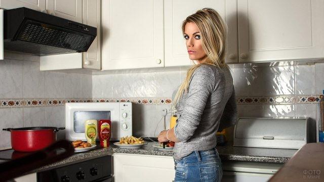 Блондинка готовит обед на кухне