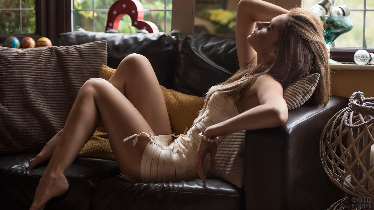 Блондинка в свободной позе на диване