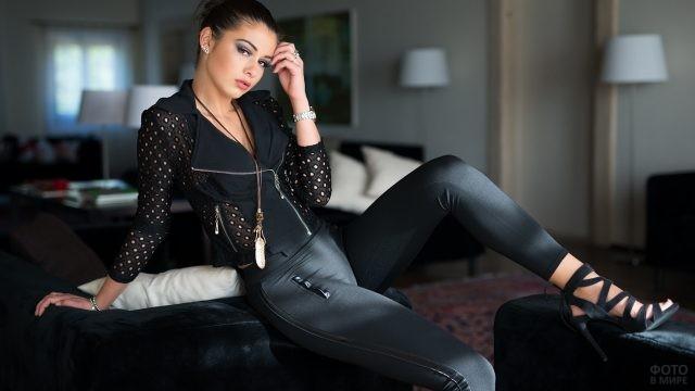 Брюнетка в чёрной одежде сидит на спинке дивана