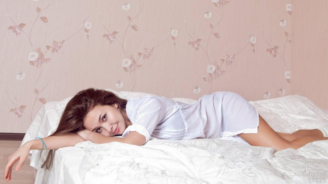 Девушка нежится на кровати
