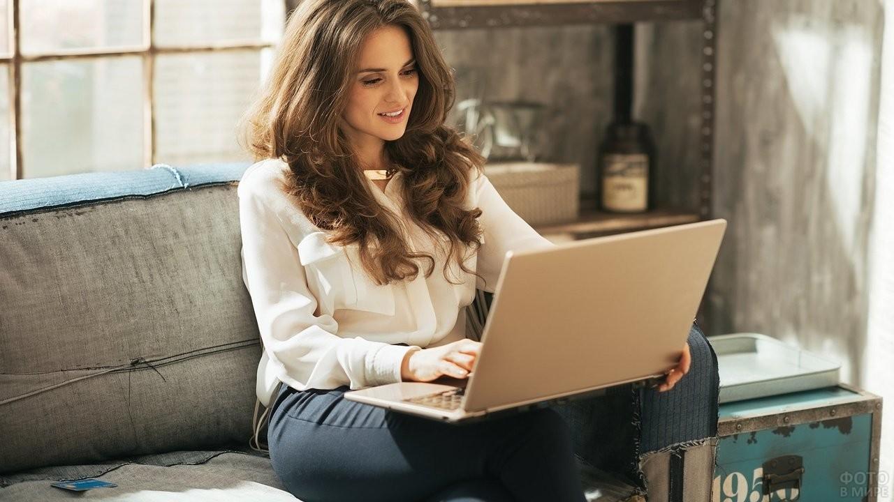 Девушка работает за ноутбуком у себя дома