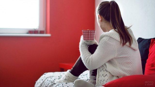 Девушка с кружкой в руках смотрит в окно