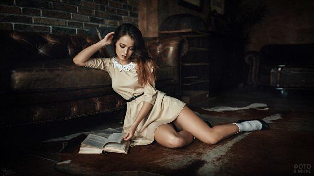 Девушка сидит с книгой на полу