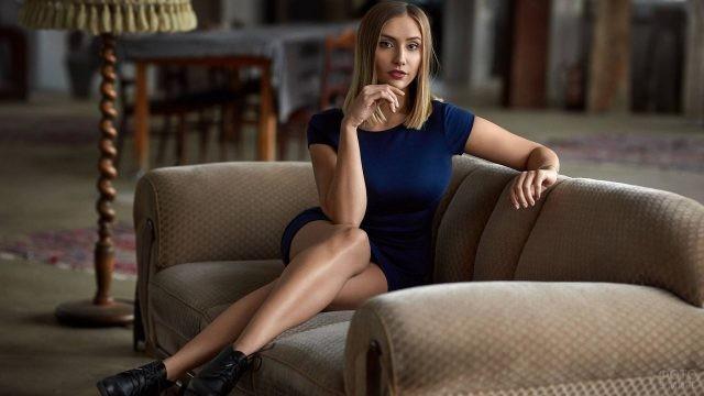 Девушка сидит в гостиной на диване