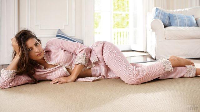 Шатенка в розовой пижаме лежит на полу