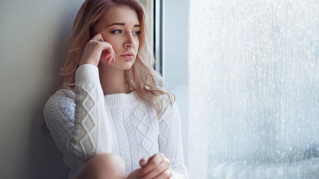 Задумчивая блондинка сидит возле окна