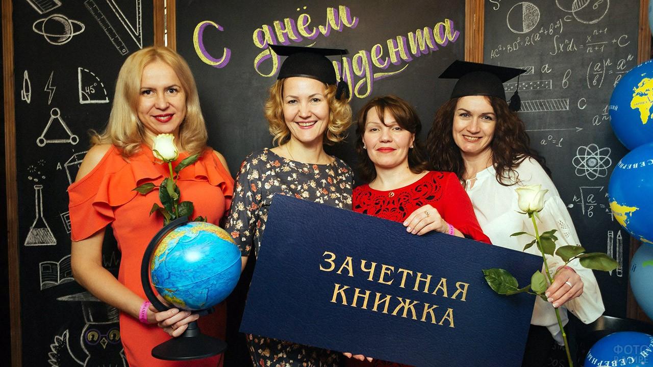Преподавательницы ВУЗа в праздничной фотозоне с макетом зачётной книжки