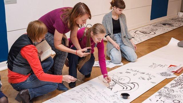 Студенты оставляют пожелания и рисунки на праздничной стенгазете