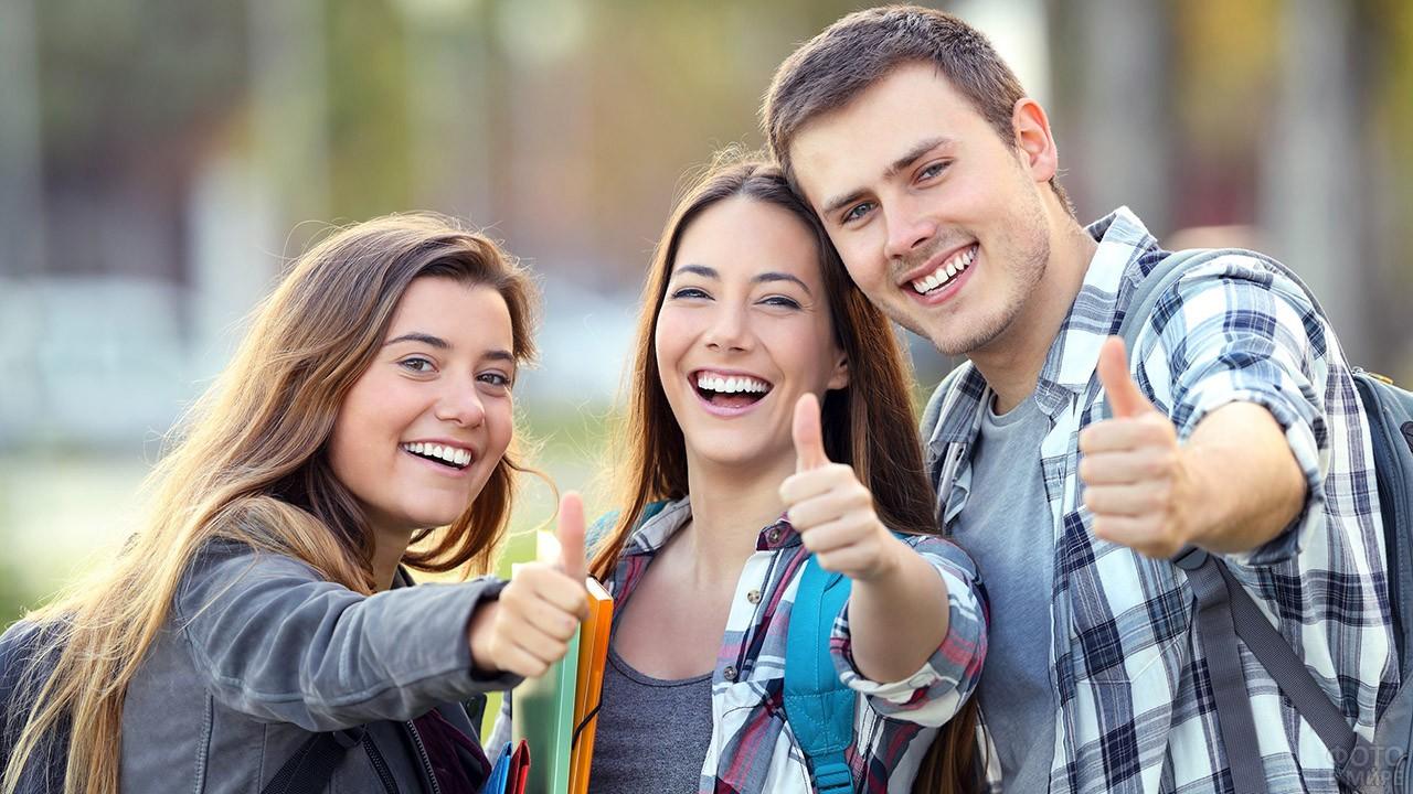 Трое счастливых студентов показывают палец вверх