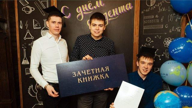 Трое студентов в фотозоне с макетом зачётки
