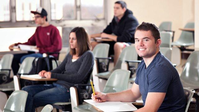 Улыбающийся студент в аудитории