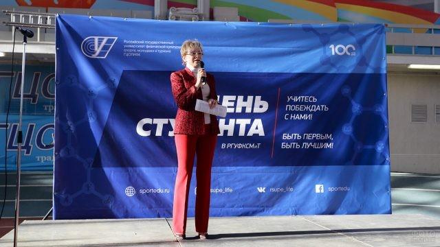 Женщина-ректор на сцене студенческого праздника